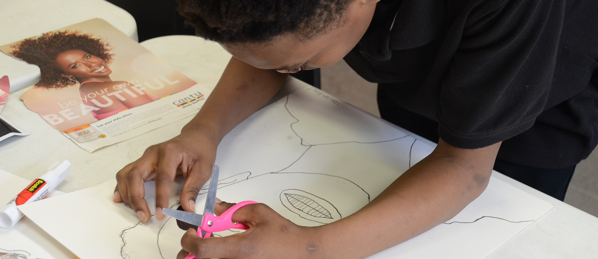 An MYDC student draws a picture.